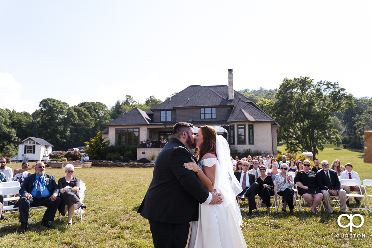 The first kiss during the outdoor wedding ceremony in Asheville,NC.