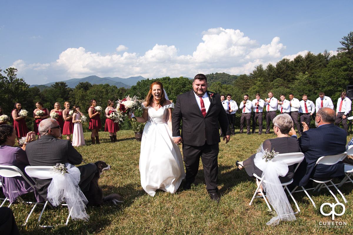 Bride and groom walking back down the aisle with the mountains behind them during the outdoor wedding ceremony in Asheville,NC.
