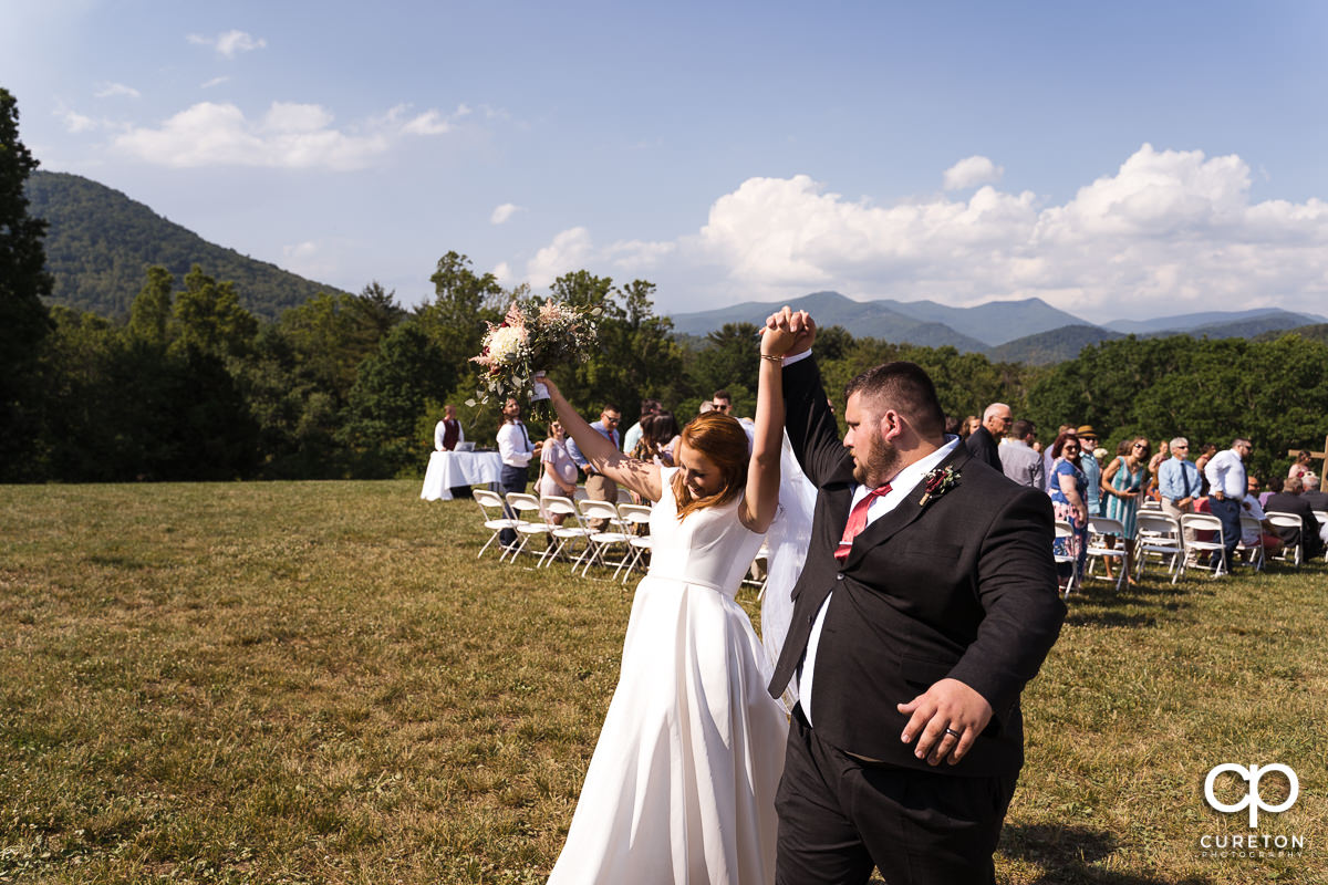 Bride and groom celebrating their vows during the outdoor wedding ceremony in Asheville,NC.