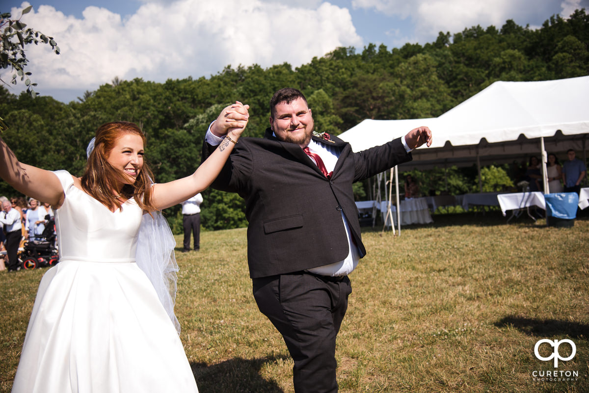 Happy bride and groom walking back down the aisle.