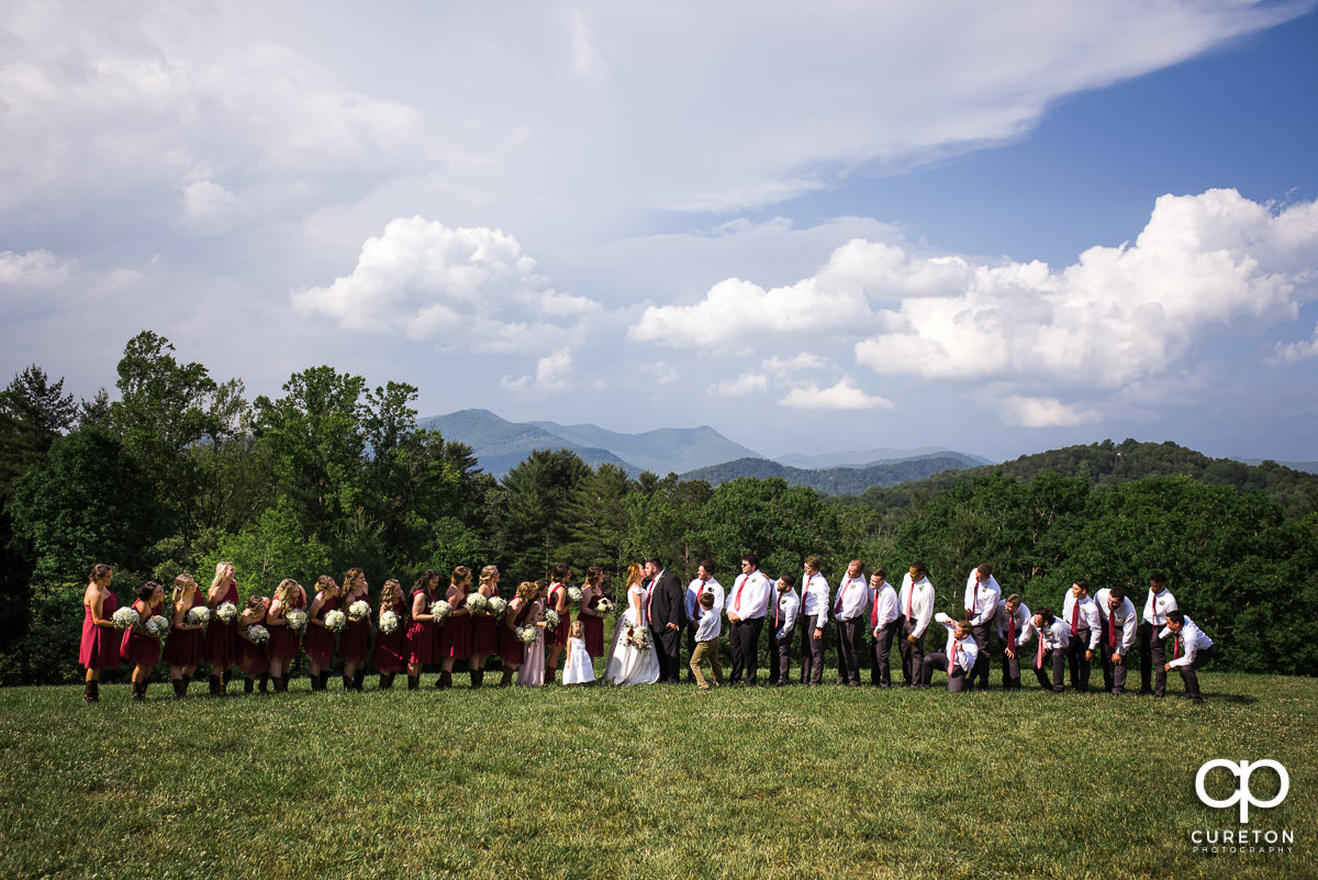 Bride and groom kissing in front of the wedding party at the outdoor wedding in Asheville,NC.