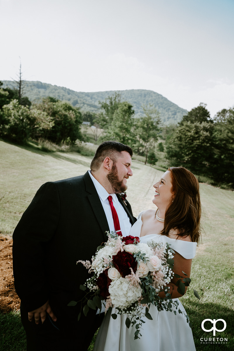 Bride and groom smiling at each other at the outdoor wedding in Asheville,NC.