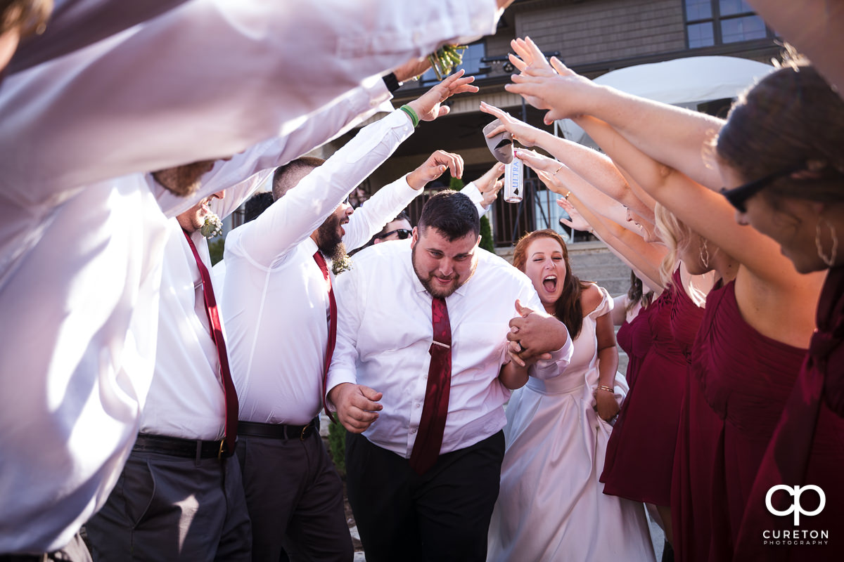 Bride and groom making a grand entrance to the reception through a tunnel of hands.