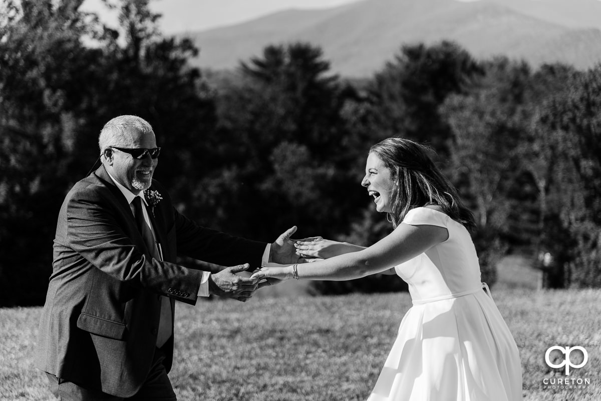Bride dancing and laughing with her dad at the reception.