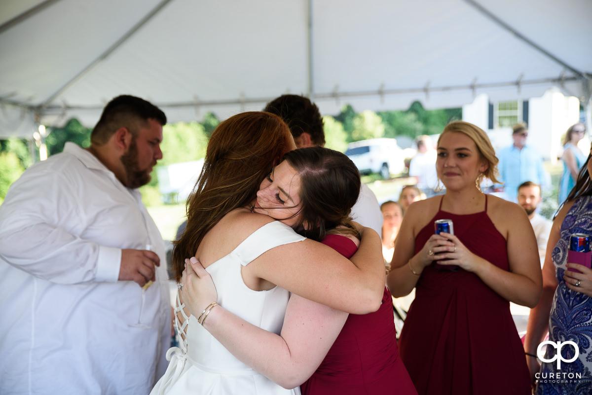 Bride hugging a bridesmaid.