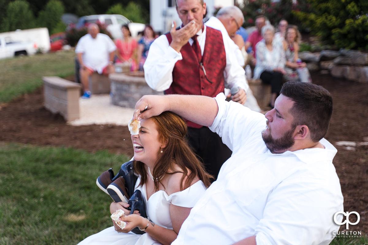 Groom smashing cake on the bride.