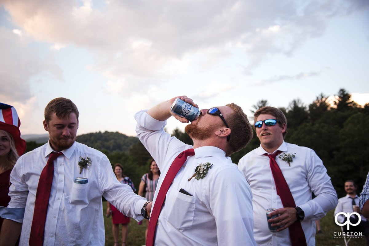 Guests playing the Thunderstruck drinking game at the wedding.