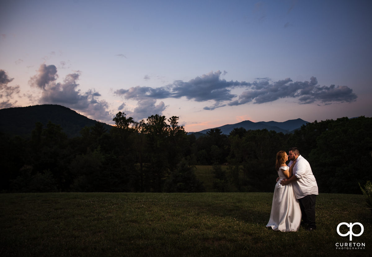 Bride and groom kissing during a mountain sunset.