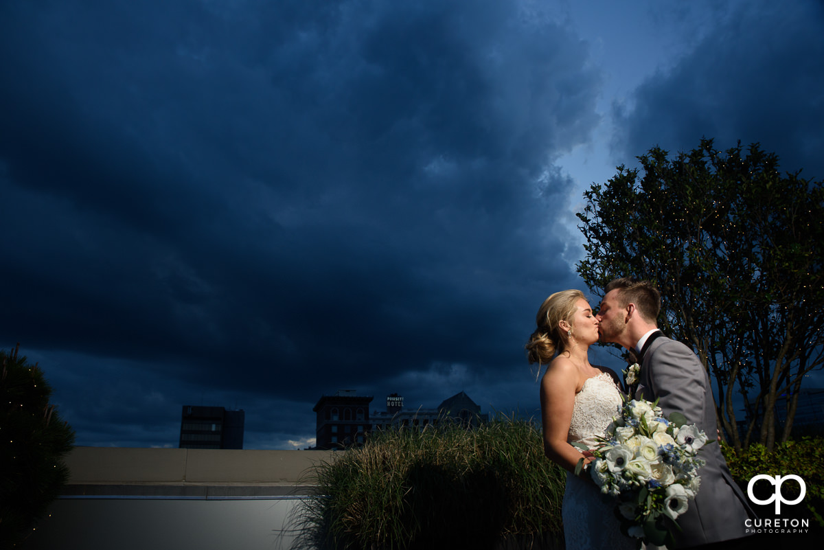 Bride and groom kissing at sunset during their wedding reception at Avenue in Greenville,SC.