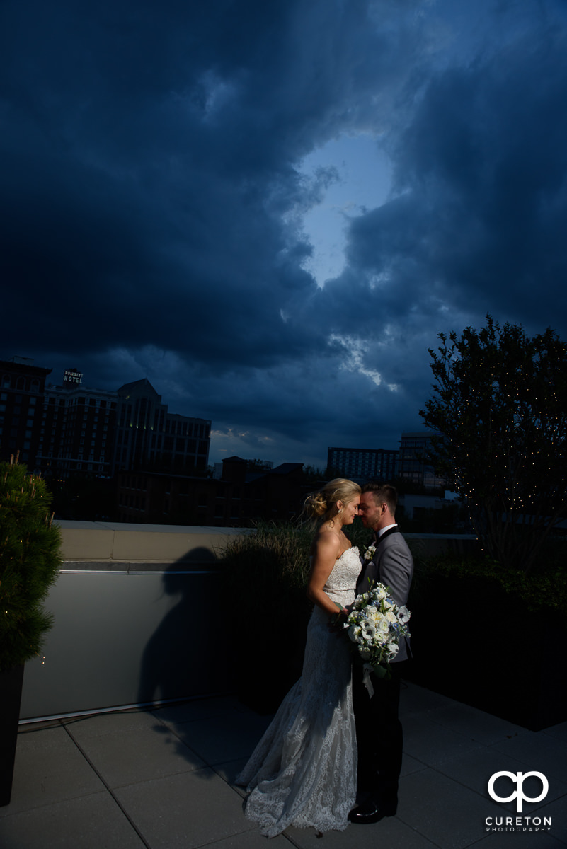 Bride and groom snuggling on a rooftop at sunset in downtown Greenville ,SC.