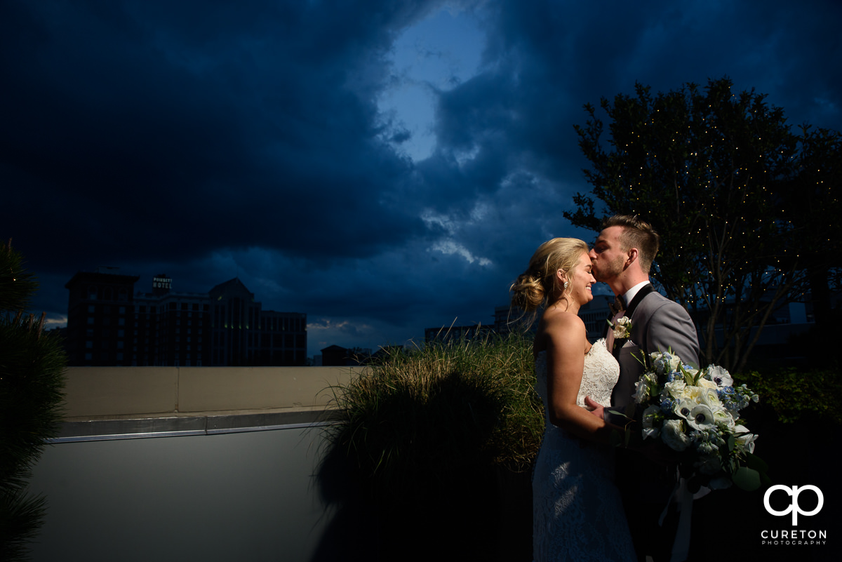 Groom kissing his bride on teh forehead after their wedding on the rooftop at Avenue in downtown Greenville,SC.