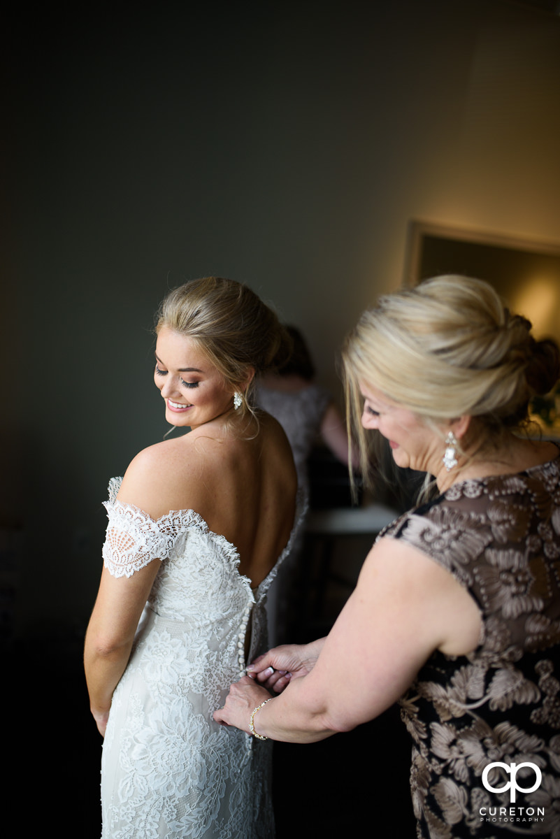 Bride's mother helping her into her wedding dress.
