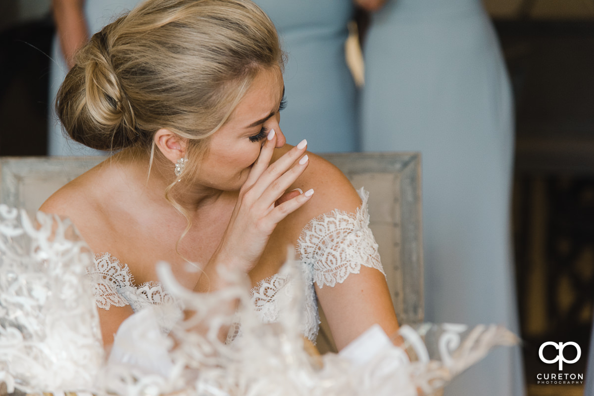 Bride tearing up while reading a card on her wedding day.