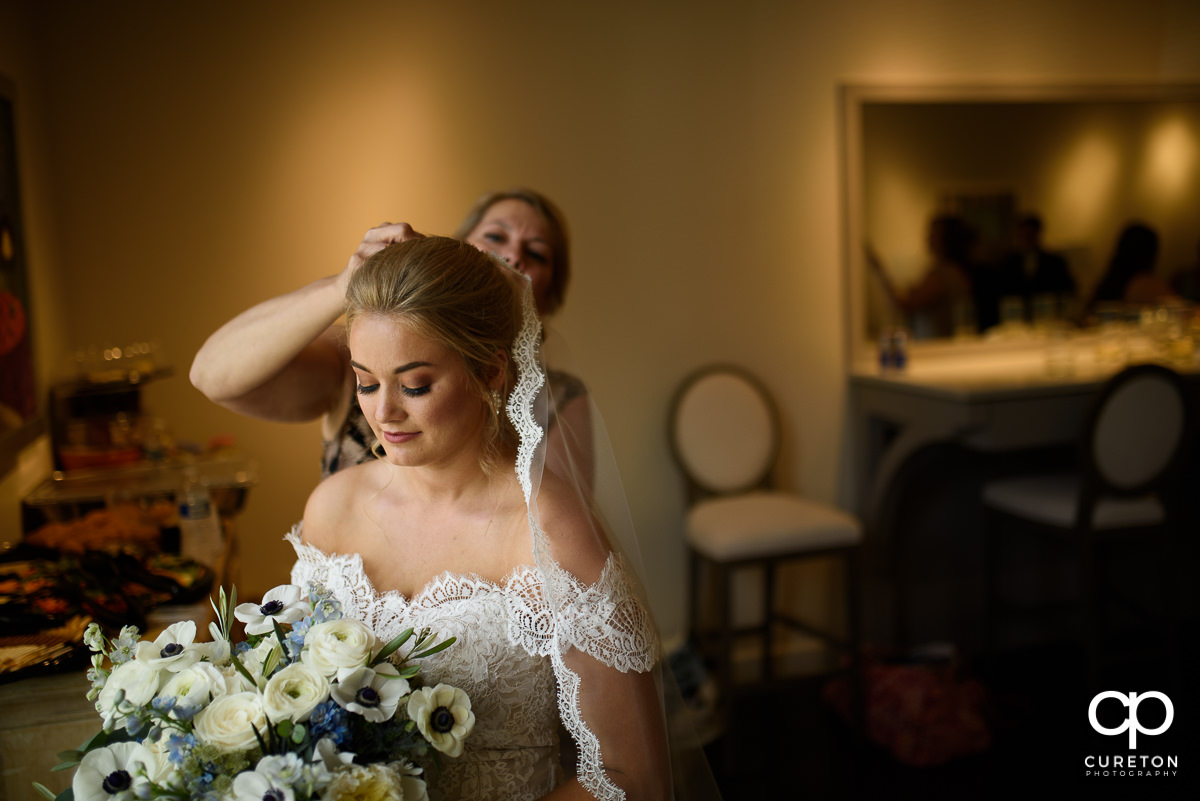 Bride putting her veil on.