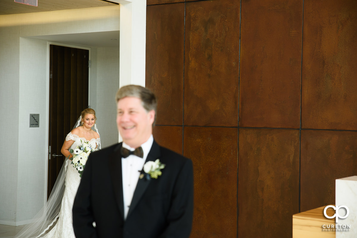 Bride walking up during first look with her father at Avenue in Greenville,SC.