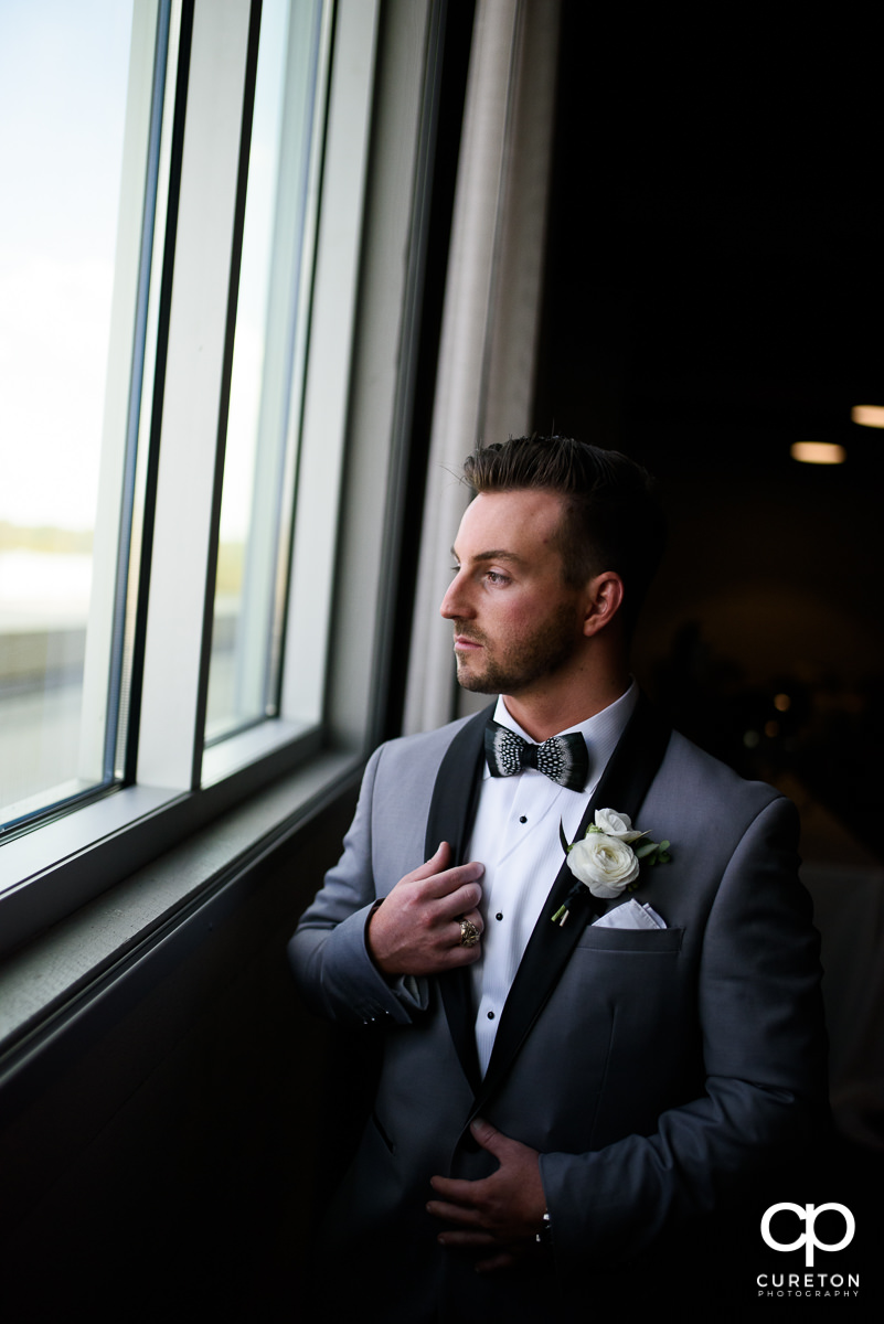 Groom looking out the window at Avenue Greenville.