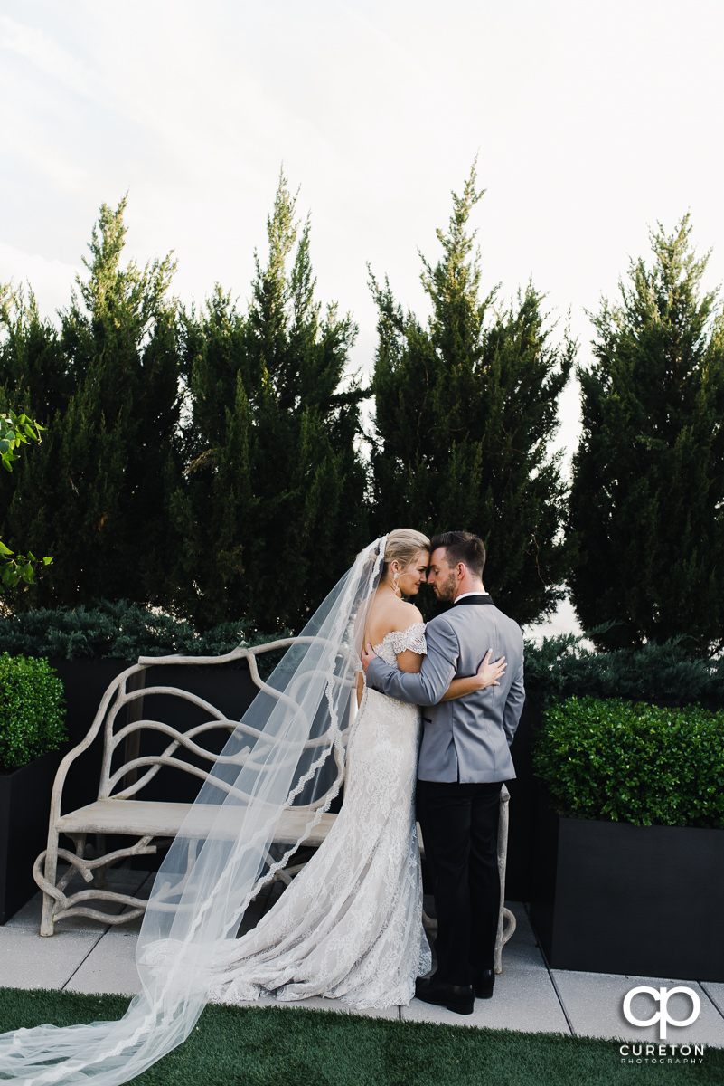 Bride and groom hugging as her long veil blows into the wind after their downtown Greenville,SC rooftop wedding at Avenue.