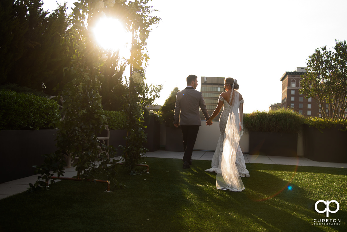 Bride and groom walking into the sunset after their downtown Greenville,SC rooftop wedding at Avenue.