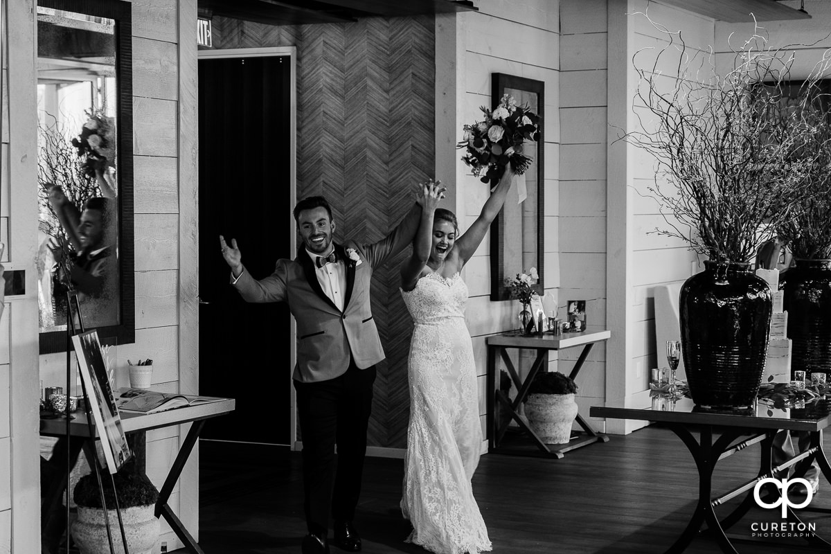 Bride and groom cheering as they are announced into their reception.