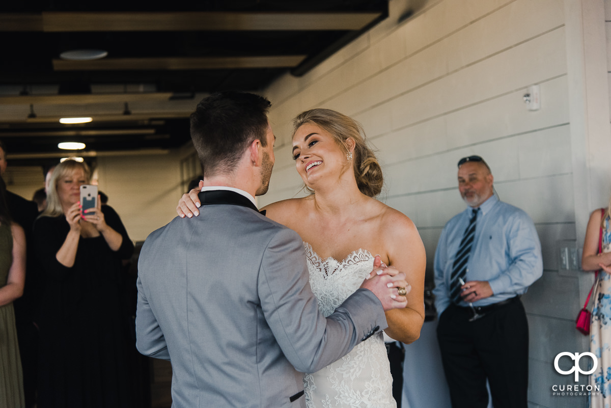 Bride smiling at her groom during their first dance at the wedding reception.