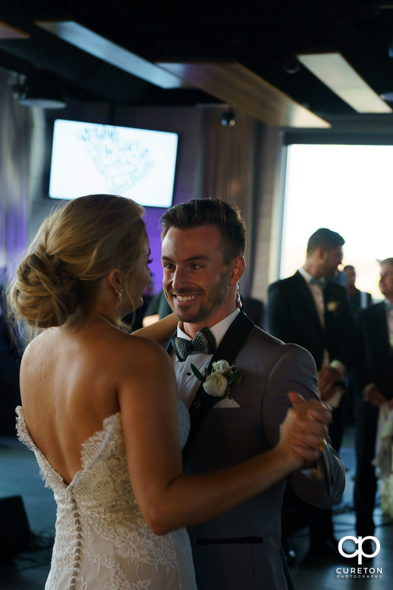 Groom smiling at his bride during their first dance at the wedding reception.
