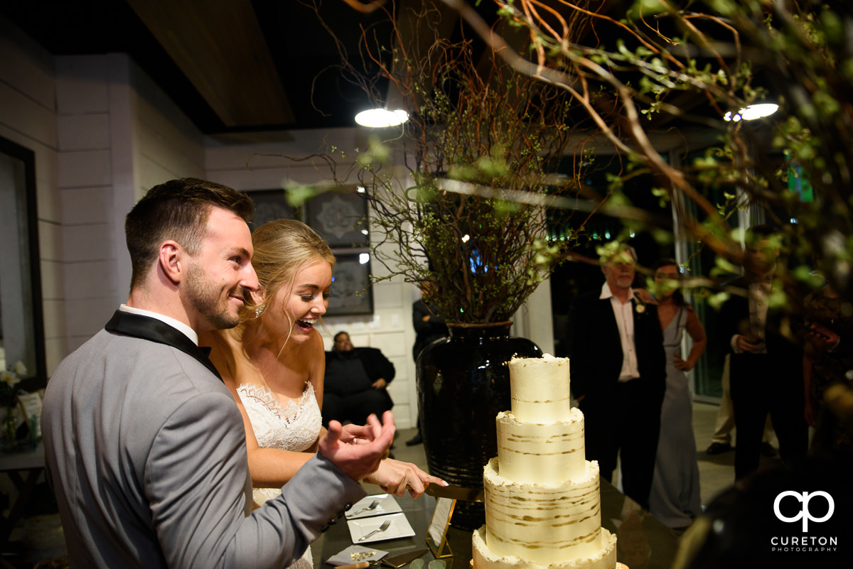 bride and groom laughing while cutting cake.