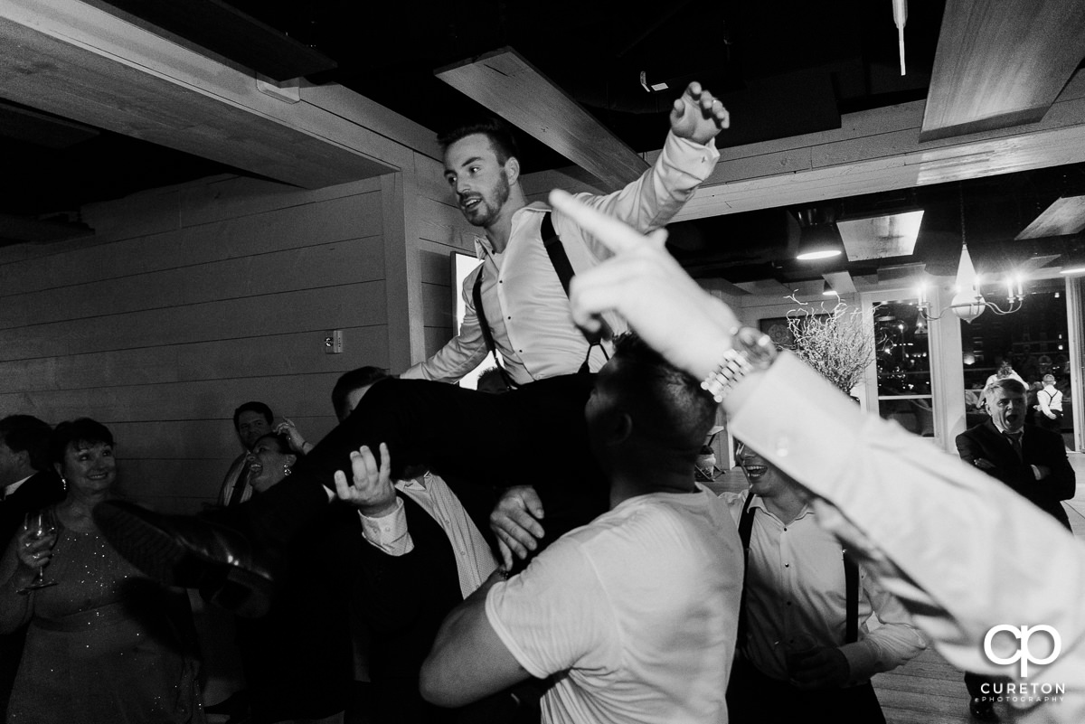 Groom being lifted above the dance floor at his wedding reception.