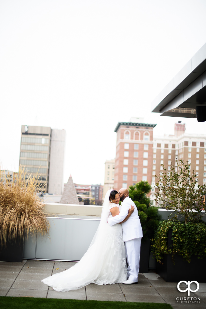 Groom kissing his bride while viewing the downtown Greenville SC skyline during their wedding at Avenue .