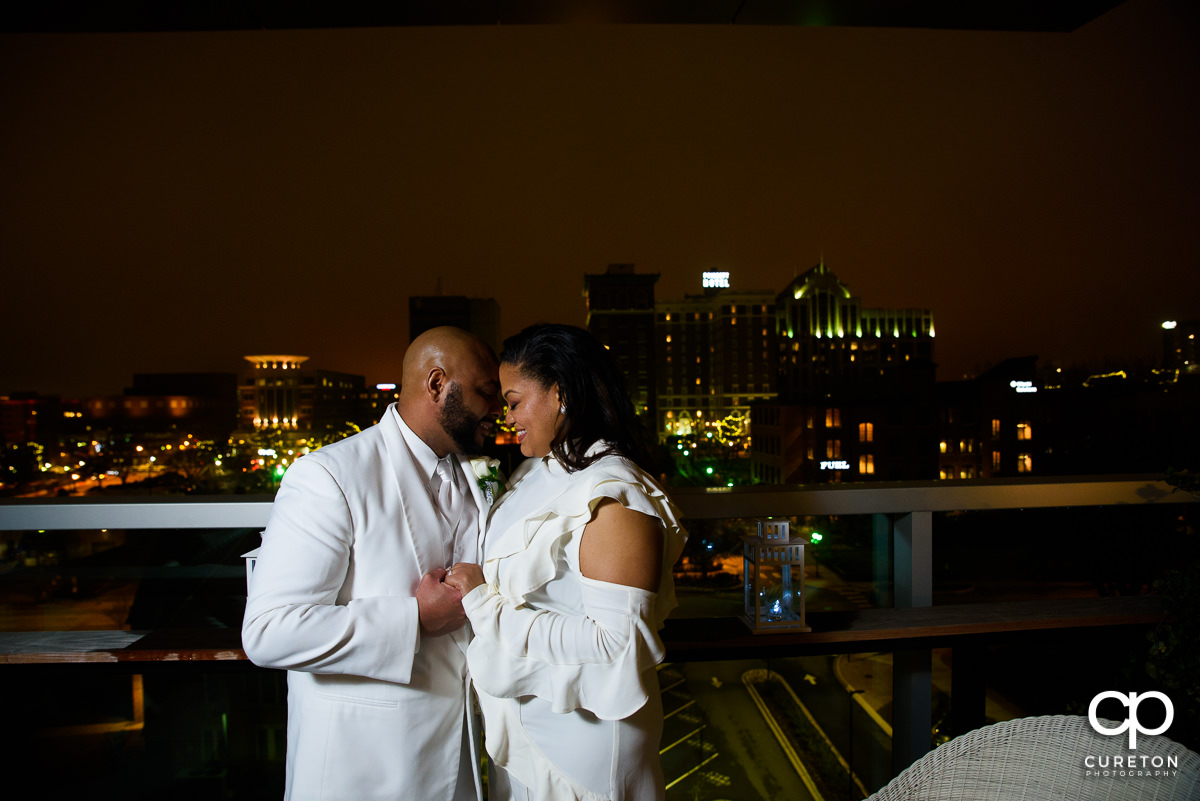Bride and groom kissing with the night skyline of Greenville in the background.