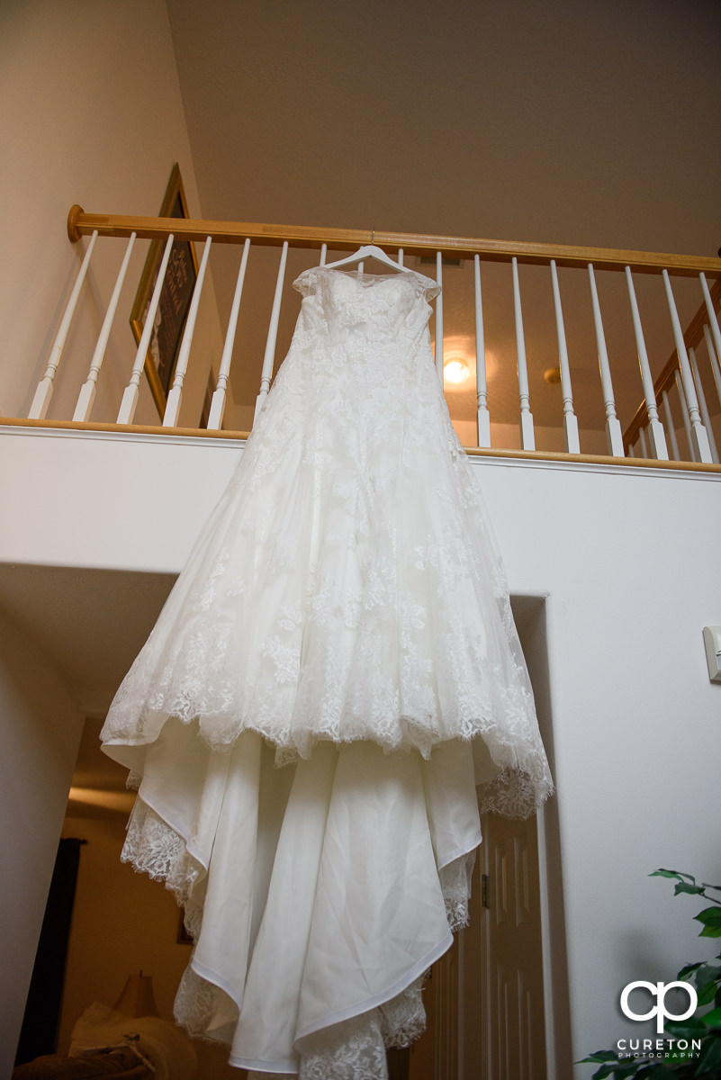 Bridal dress hanging on a staircase.
