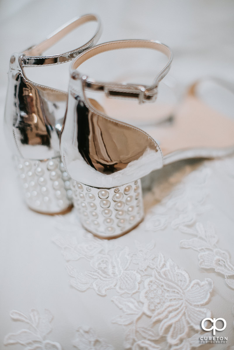 Bride's shoes sitting on her dress.