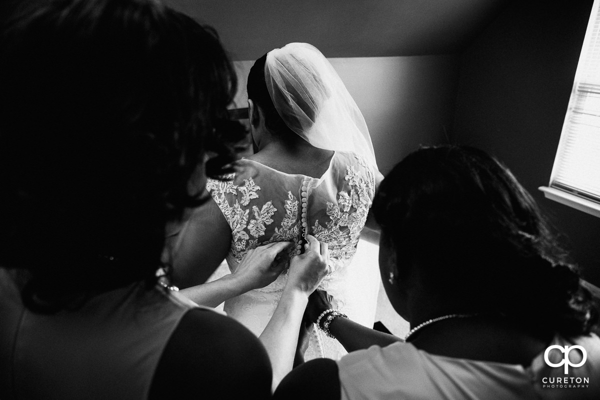 Bride getting into her dress with the help of her bridesmaids.
