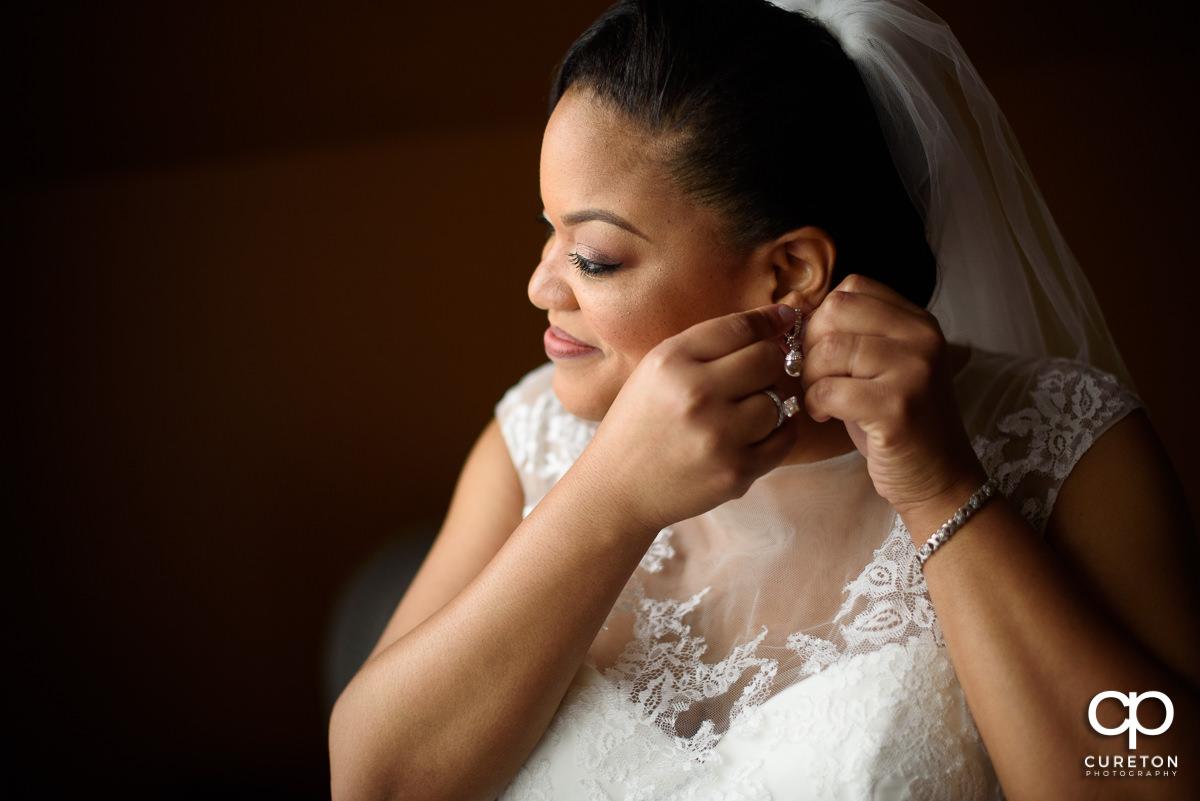 Bride putting her earrings in.