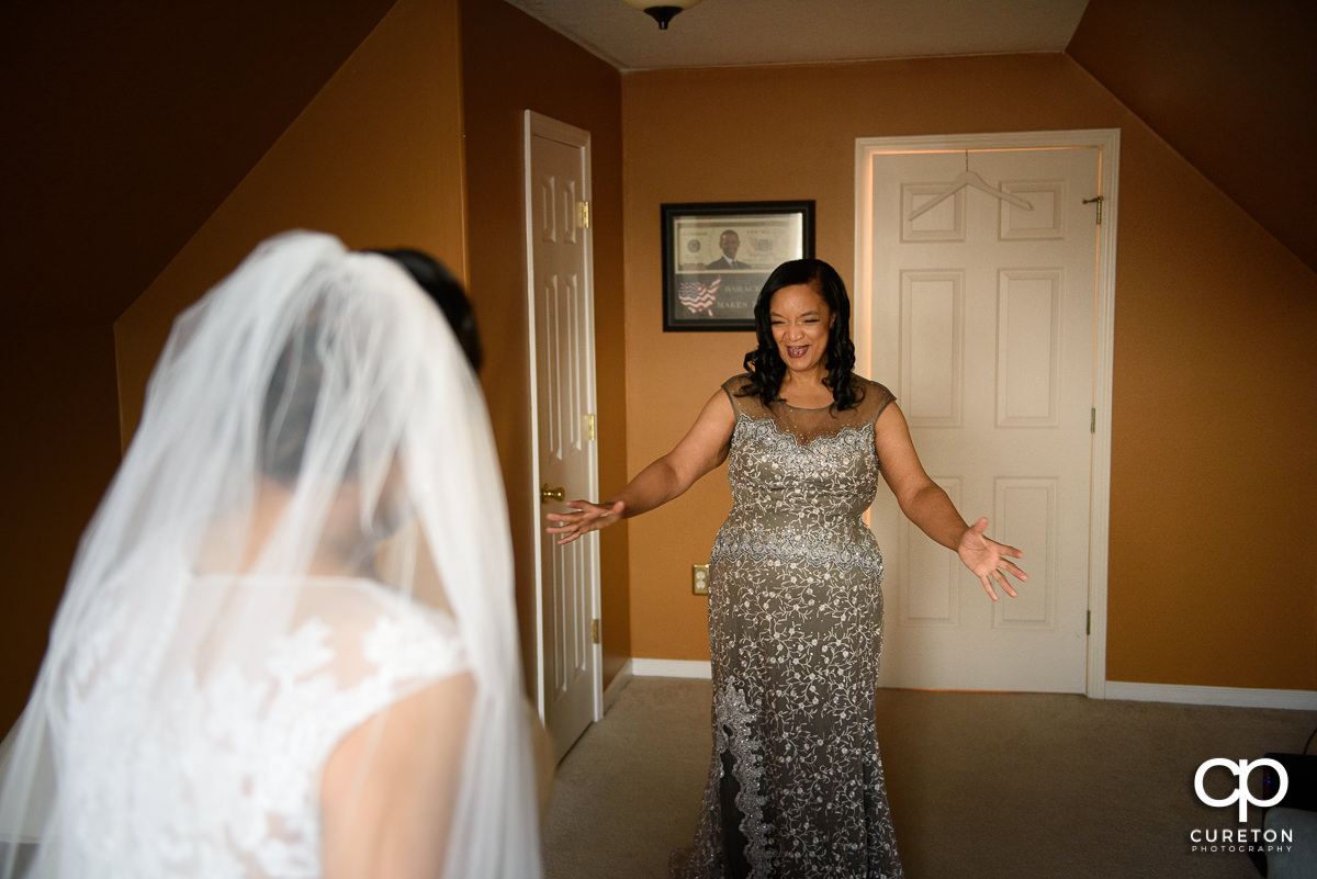 Bride's mom seeing her daughter in the dress on her wedding day.