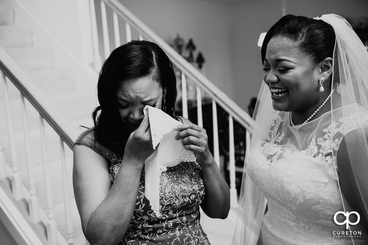 Bride's mom tearing up while receiving a gift from her daughter.