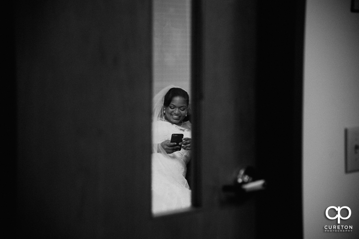 Bride texting and smiling though a window before the wedding ceremony.