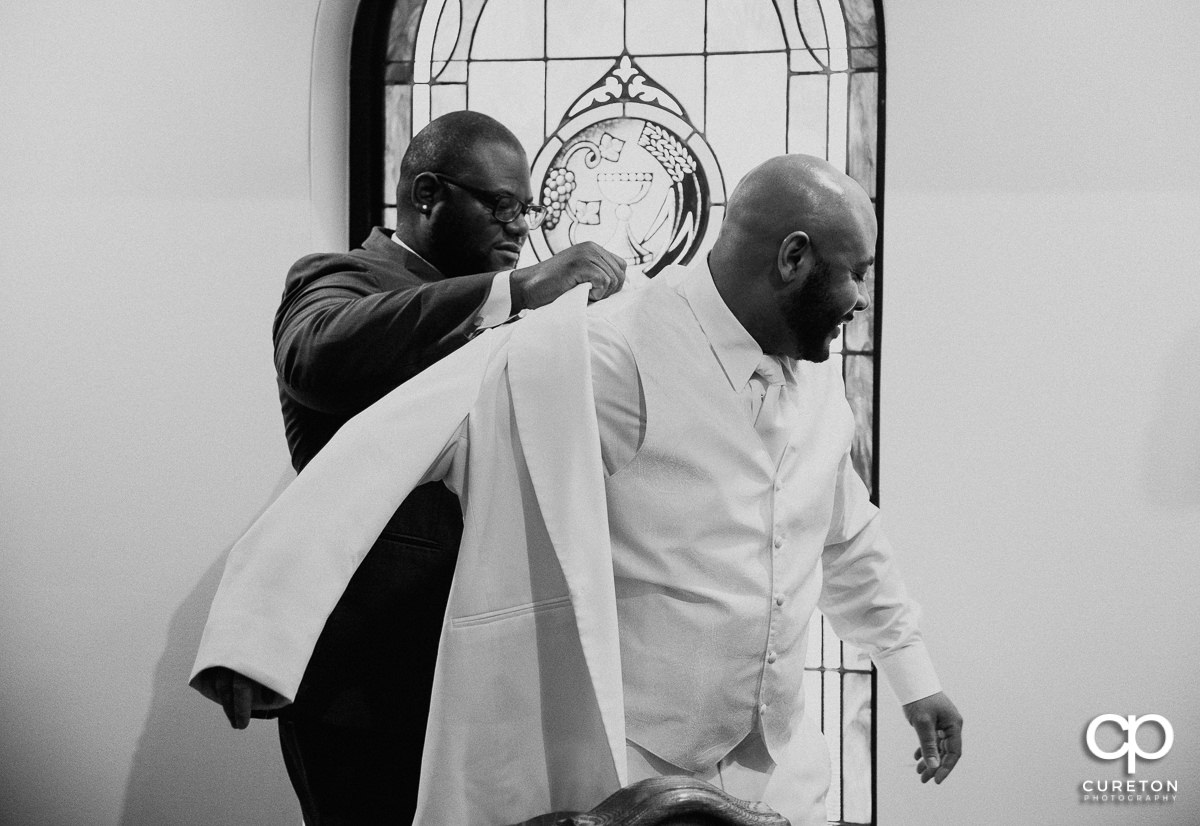 Groom getting helped into his jacket.