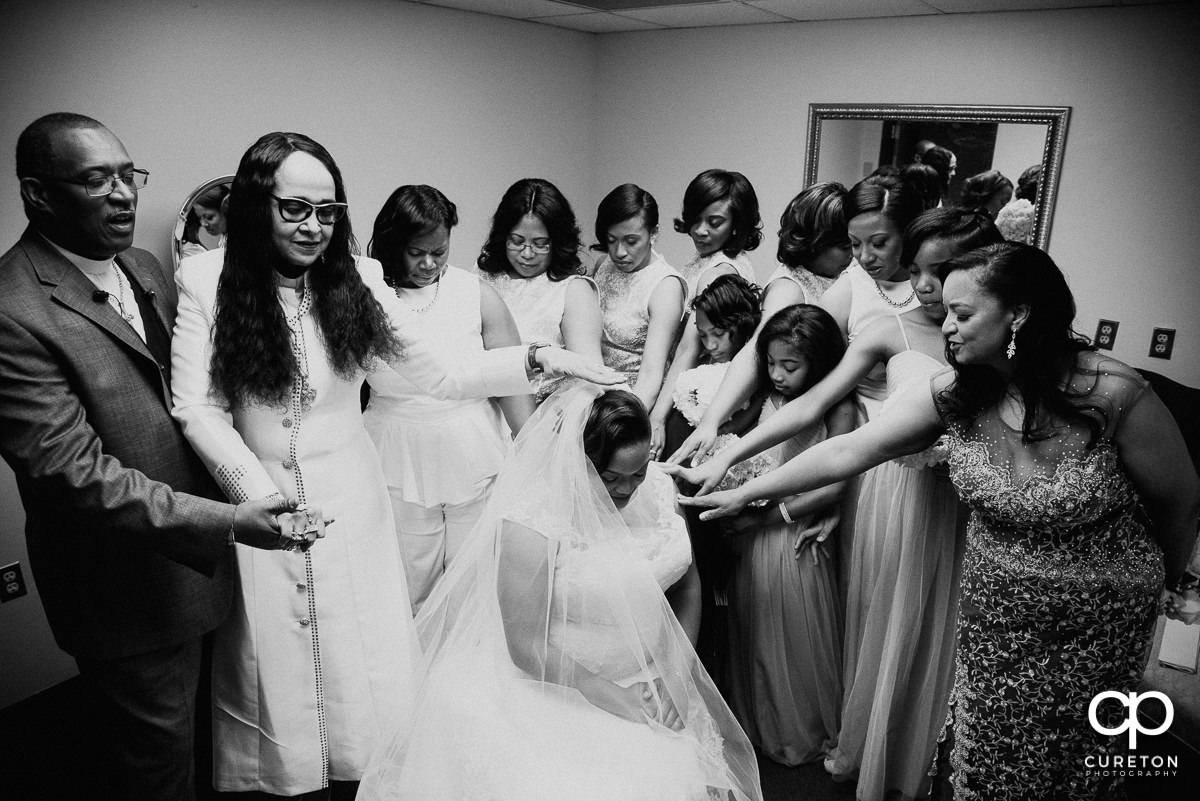 Bridesmaids and family praying over the bride before the ceremony.