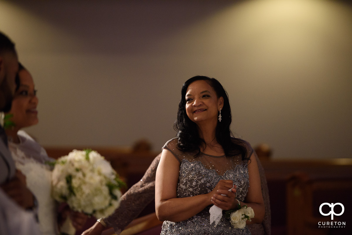 Bride's mother smiling as her daughter is walked down the aisle.