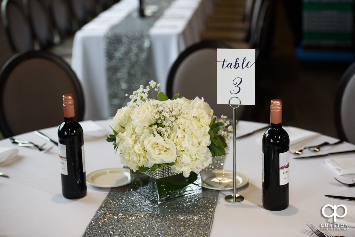Floral arrangement and table number on a table at the reception at Avenue in downtown Greenville.