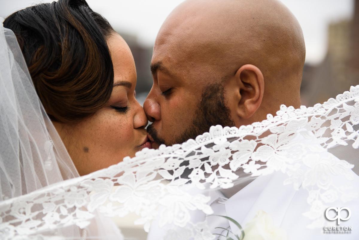 Bride and groom kissing behind her veil.