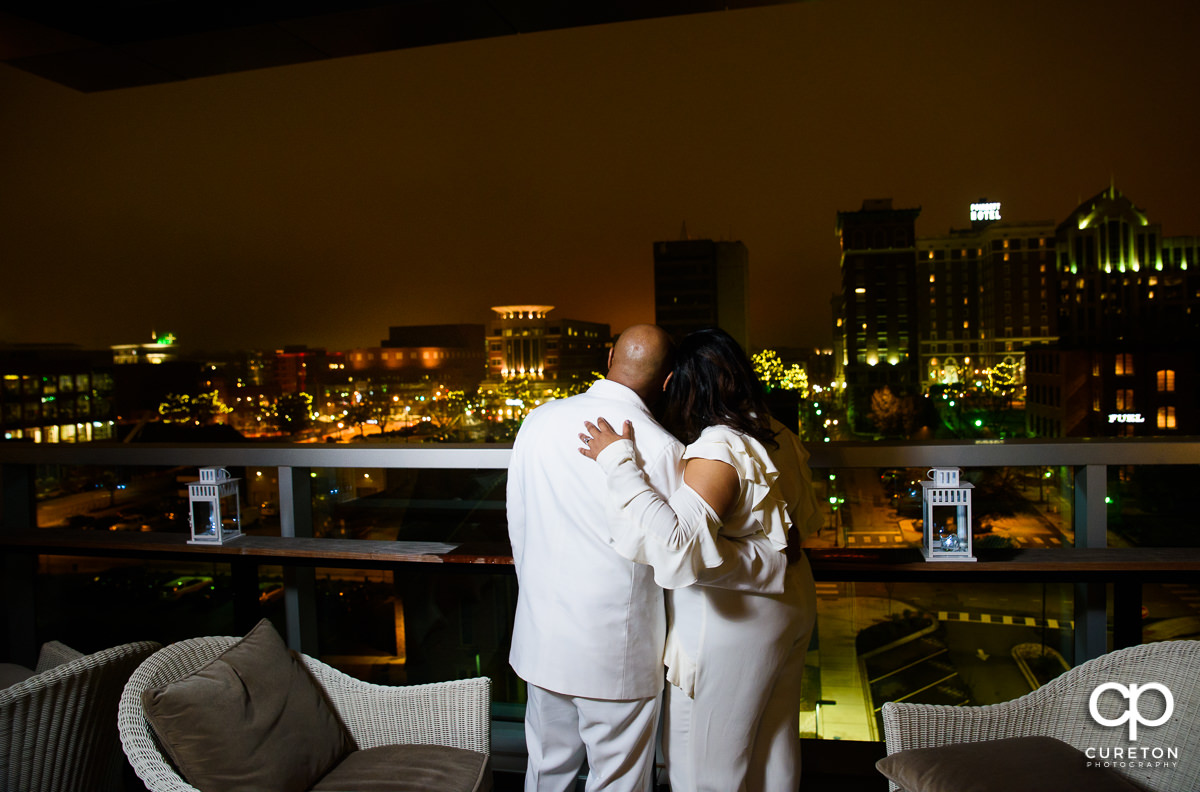 Bride and groom looking into the night on the roof.