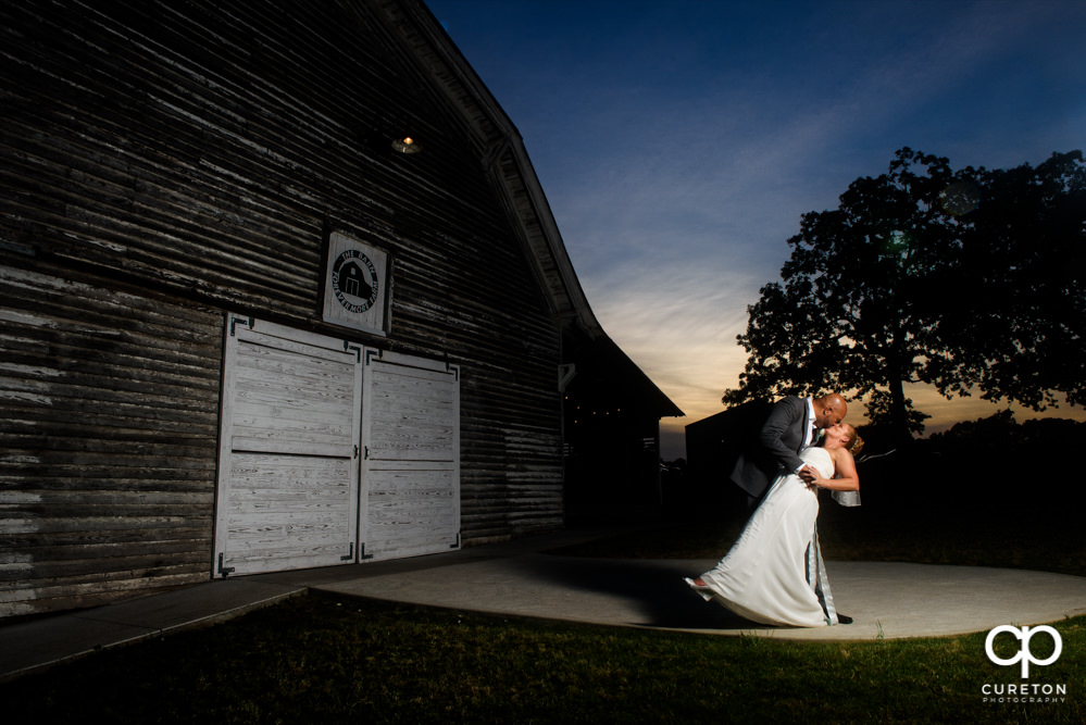 Bride and groom kissing at the Barn at Forevermore Farms after their rustic wedding.