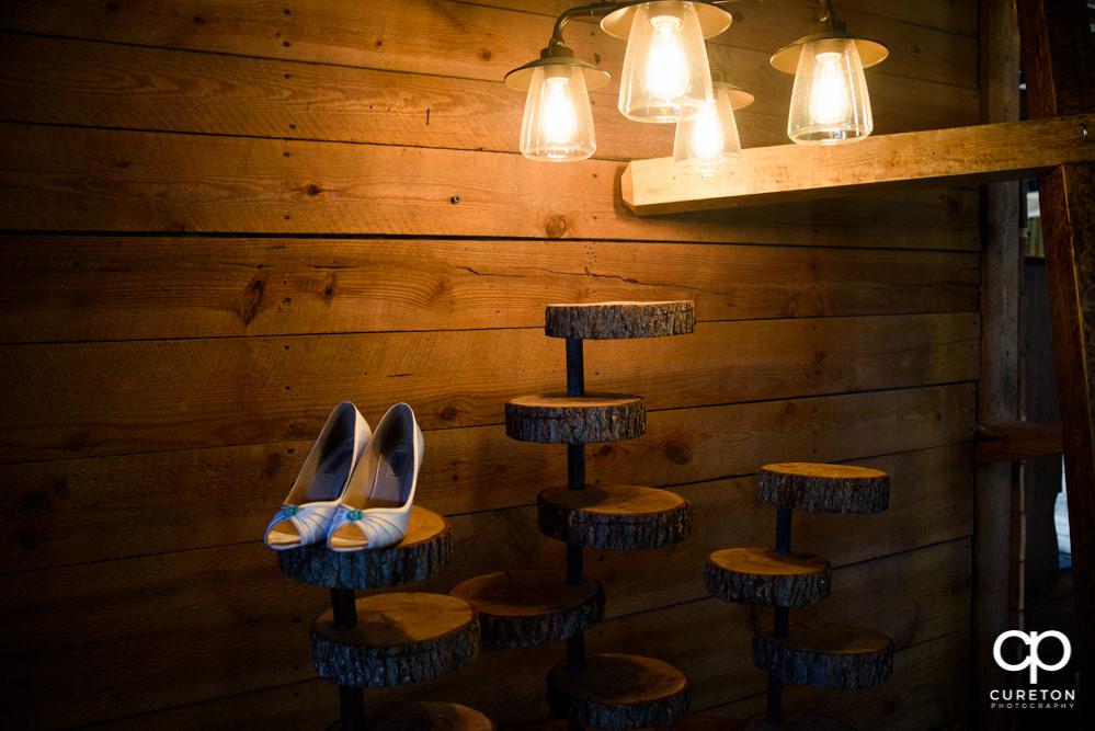 Bride's shoes under Edison light bulbs.