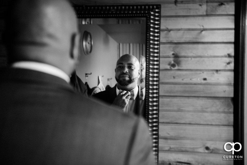 Groom fixing his tie in the mirror.
