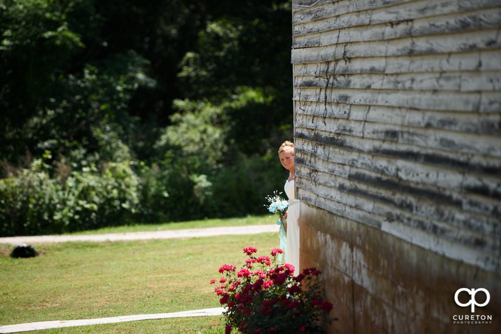 Bride peeking around the corner of the barn to see her groom.