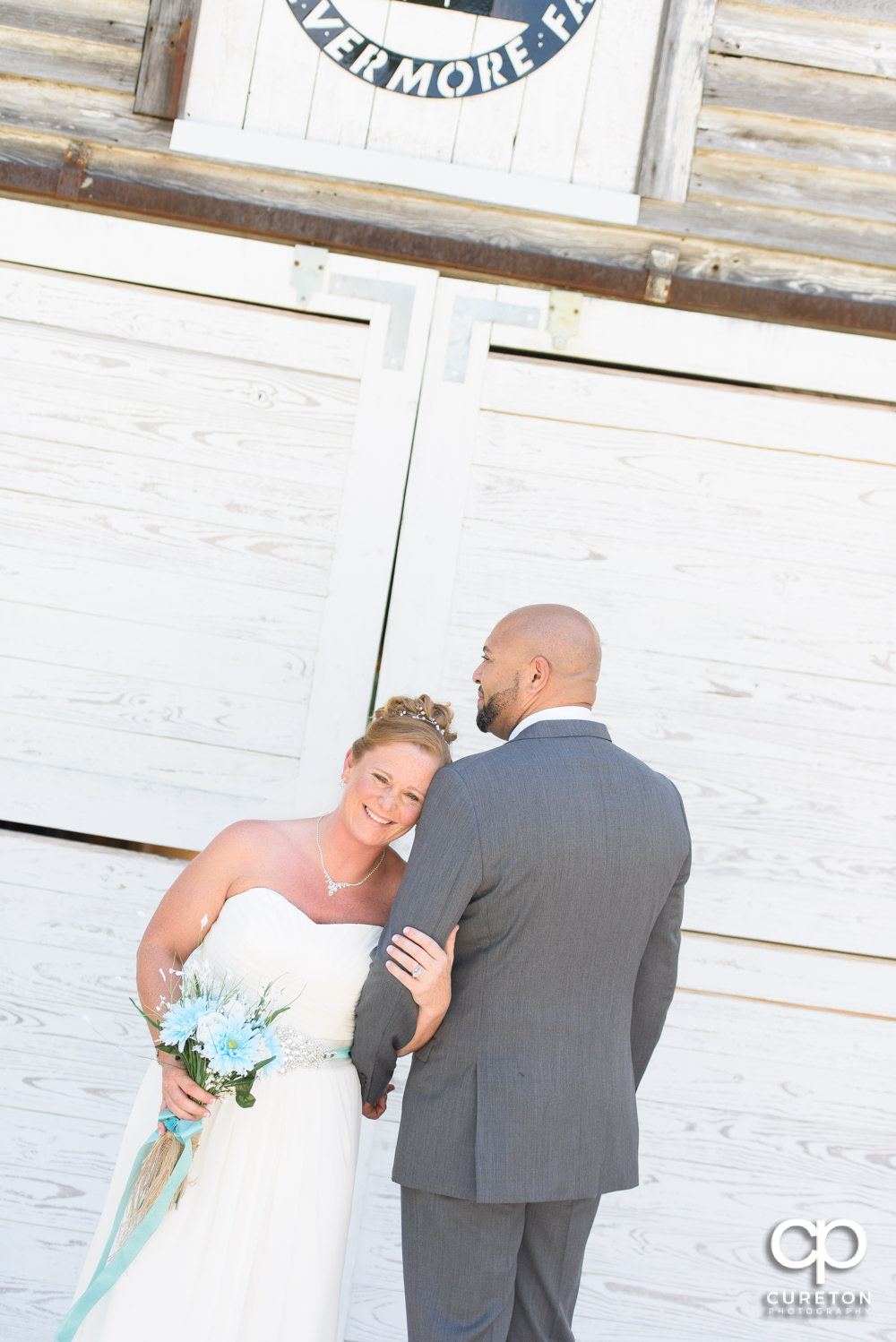 Bride and groom in front the Barn at Forevermore Farms.