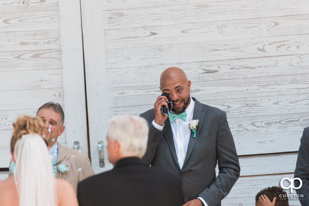 Groom crying when he's sees his bride walking down the aisle.