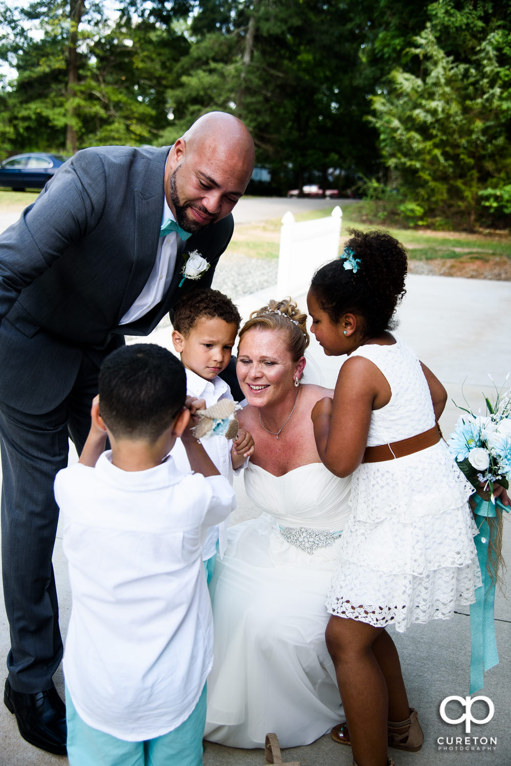 Bride and groom celebrating with their children after their wedding.