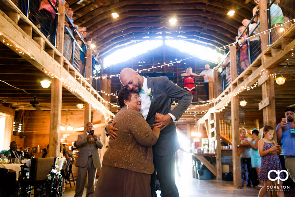 Groom and mother dance at their wedding reception at The Barn at Forevermore Farms.